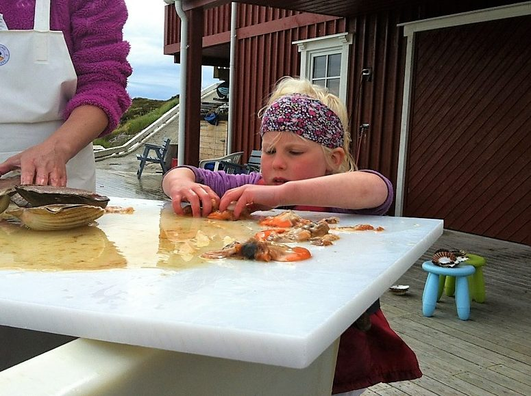 Barn elsker å feriere i Øyrekka - her et barn som ordner opp kamskjell